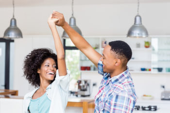happy young couple dancing in kitchen